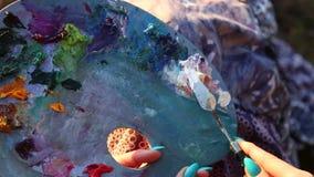 Żeńskiej artysta ręki mienia farby zbliżenia nożowy tło zbiory wideo