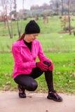 Żeńskiej atlety kaleczenie od urazu kolana na zimnym zima dniu na stażowym śladzie miastowy park obrazy royalty free
