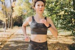 Żeńskiej atlety kobiety biegacz jest ubranym bezprzewodowe słuchawki słucha muzyka na mądrze telefonie zdjęcia royalty free