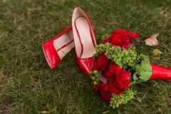 Żeńskiej mody ślubu czerwoni buty z panny młodej ` s bukietem czerwone róże i zielone jagody na zielonej trawy tle Zdjęcia Stock