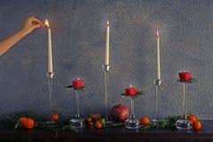 Żeńskiej ręki oświetleniowa świeczka na stole z owoc Fotografia Royalty Free