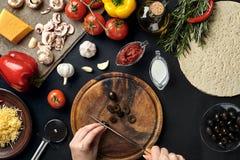 Żeńskiej ręki rżnięte oliwki na drewnianej desce na kuchennym stole wokoło kłamstwo składników dla pizzy: warzywa, ser i pikantno Fotografia Royalty Free