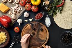 Żeńskiej ręki rżnięte oliwki na drewnianej desce na kuchennym stole wokoło kłamstwo składników dla pizzy: warzywa, ser i pikantno Obrazy Stock