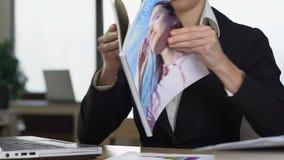 Żeńskiej sekretarki czytelniczy magazyn zamiast pracuje, siedzący przy biurowym biurkiem, gnuśność zbiory wideo