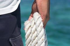 Żeglarza mienia arkana przeciw błękitnemu morzu obraz stock