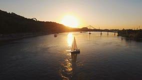 Żeglowanie jacht z biel żaglami pływa wzdłuż rzeki przy zmierzch anteną zdjęcie wideo