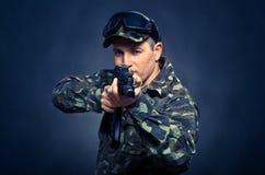 Żołnierz celuje maszynowego pistolet na błękitnym tle fotografia stock