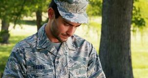 Żołnierz używa cyfrową pastylkę w parku zdjęcie wideo