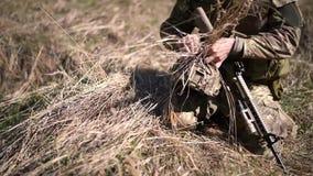 Żołnierz w wojennym harcerzu stawia suchej trawy w kamuflażu hełmie tworzyć kamuflaż w lesie zbiory