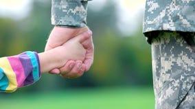 Żołnierza i małej dziewczynki mienia ręki, zakończenie w górę zbiory wideo