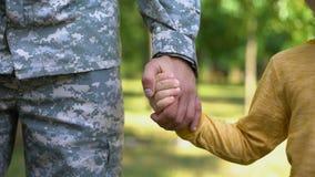 Żołnierza mienia chłopiec ręki, wojsko broniąca bezpieczna przyszłość, rodzinna więź zbiory