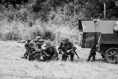 Żołnierze chuje za orężnym pojazdem czarny i biały Zdjęcia Stock