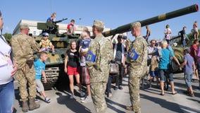 Żołnierze w wojskowego uniform wśród miastowych dzieci i dorosłych zbliżają zbiornika z wielkim działem na ulicie w lecie i zbiory wideo