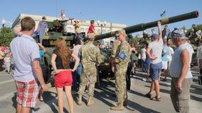 Żołnierze w wojskowego uniform wśród miastowych ludzi blisko zbiornika z wielkim działem w centrum miasto w lecie zbiory wideo