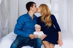 Żona i mąż tenderly całujemy each inny i między one siedzimy ich małej córki Rodzinna harmonia postawa zdjęcie royalty free