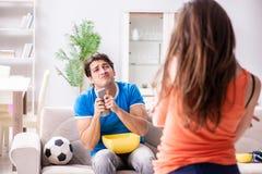 Żona nieszczęśliwa który ogląda futbol mąż obraz royalty free
