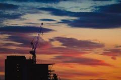 Żuraw i budynek w chmurnym wieczór fotografia stock
