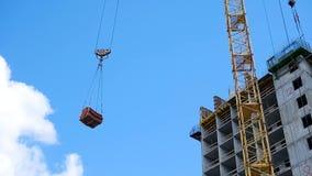 Żurawia i budynku budowa przeciw niebieskiemu niebu ciężkiego ładunku obwieszenie na haczyku żuraw na budowie zbiory