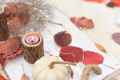 życie ciągle jesieni Kolorowi liście, świeczka i biała mini bania na lekkiej drewnianej tacy, zdjęcie royalty free