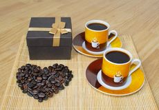 1 życie wciąż Dwa filiżanki kawy, pudełko z prezentem i serce robić od kawowych fasoli, zdjęcia royalty free