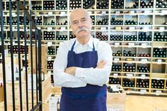 Życzliwa dojrzała sprzedawca pozycja w wino domu obrazy royalty free