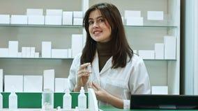 Życzliwa farmaceuta opowiada kamera z butelką pigułki Obrazy Royalty Free
