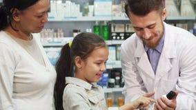 Życzliwa farmaceuta pokazuje małej dziewczynki jeden tubki zbiory wideo