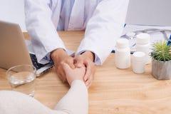 Życzliwe doktorskie ręki trzyma cierpliwego ręki obsiadanie przy biurkiem f Zdjęcie Royalty Free