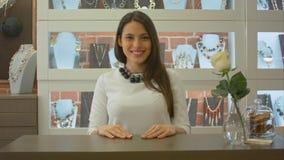 Życzliwego żeńskiego sprzedawcy śliczny ono uśmiecha się, patrzejący kamerę w sklepie jubilerskim Fotografia Royalty Free