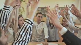 Życzliwi kolega z klasy siedzą przy biurkiem i podnoszą ich ręki wpólnie Rosjanin szkoła Student Collegu pracy zespołowej sztaplo zbiory