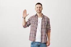 Życzliwy atrakcyjny męski sportowiec podnosi palmy w modny odzieżowym, szkła i, ono uśmiecha się obrazy royalty free