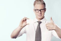 Życzliwy biznesmen daje aprobatom przy bielem opróżnia kartę. Obrazy Stock