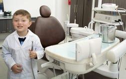 Życzliwy chłopiec dentysta z stomatologicznym wyposażeniem Obraz Royalty Free