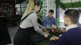 Życzliwy kelner w fartuchu słuzyć zakąskę młodzi ludzie uspołecznia w cukiernianym obsiadaniu przy stołem zdjęcie wideo
