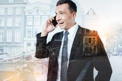 Życzliwy mężczyzna patrzeje radosny podczas gdy opowiadający na telefonie obraz royalty free