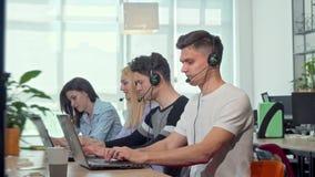 Życzliwy młody człowiek ono uśmiecha się kamera, pracuje przy obsługi klientej centrum telefonicznym zbiory wideo