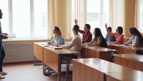 Życzliwy nauczyciel opowiada ucznie pyta pytania podczas gdy młodzi ludzie podnoszą ręki i odpowiadają siedzieć przy zbiory wideo
