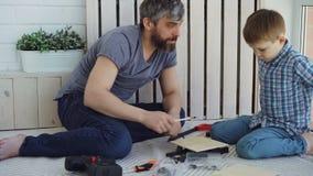 Życzliwy ojciec i mały syn jesteśmy opowiadający i roześmiani podczas gdy robić robot budowlany obsiadaniu na podłoga w domu zbiory