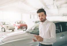 Życzliwy pojazdu sprzedawca przedstawia nowych samochody przy sala wystawową Fotografia młody męski konsultant pokazuje nowego sa obrazy stock