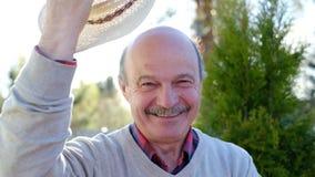 Życzliwy starszy mężczyzna stawia daleko kapeluszowych powitanie przyjaciół zdjęcie wideo