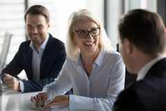 Życzliwy w średnim wieku żeński lider śmia się przy grupowym biznesowym spotkaniem obrazy royalty free