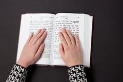 Żydowska książka z kobiety ` s ręką na czarnym tle, Tekst hebrajszczyzna, modlitwa Kobieta ono modli się z książką obraz royalty free