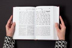 Żydowska książka z kobiety ` s ręką na czarnym tle, Tekst hebrajszczyzna, modlitwa książka tła ps czytelniczej stworzył kobietę obraz royalty free