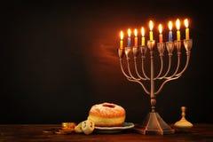 żydowski wakacyjny Hanukkah tło z tradycyjnym spinnig wierzchołkiem, menorah & x28; tradycyjny candelabra& x29; i palący świeczkę zdjęcie royalty free