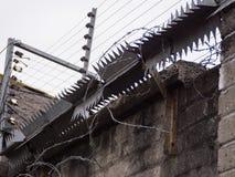 Żyletka drut, elektryczny ogrodzenie i metali kolce na ścianie, obraz royalty free