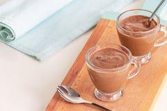 Żywienioniowy deserowy jogurtu czekoladowego puddingu filiżanek słuzyć drewniany tnący abordaż kosmos kopii zdjęcie stock