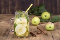 Żywienioniowy detox napój z jabłko plasterkami i nowymi liśćmi w czystej wodzie i świeżym jabłku na drewnianym stole, obraz stock