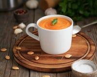 Żywienioniowy jarski lunch na tnącej desce z pietruszką, czosnek Pupmkin kremowy zupny puree w filiżance na brązu drewnianym stol zdjęcie stock