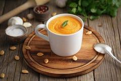 Żywienioniowy jarski lunch na tnącej desce z pietruszką, czosnek Pupmkin kremowy zupny puree w filiżance na brązu drewnianym stol zdjęcia stock