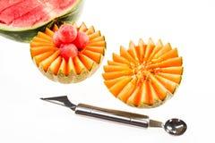 Żywienioniowy jedzenie, detox Rżnięty żółty melon i czerwień arbuz obok noża dla kędzierzawego rozcięcia na białym tle zdjęcie royalty free